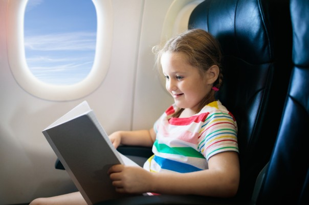 Girl reading book in airplane.jpg